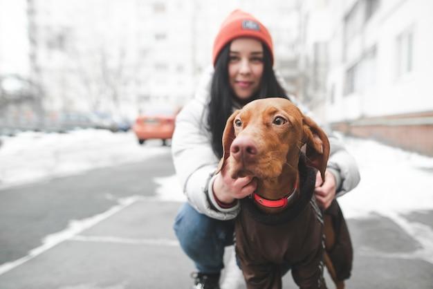 Fille douce avec une belle race de chien magyar vizsla est assis sur une rue d'hiver