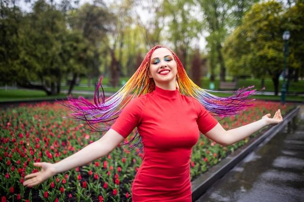 Une fille douce avec un maquillage brillant expressif et de longues tresses multicolores en robe rouge. tourbillonne dans le parc printanier sur fond de parterre de fleurs en fleurs avec des tulipes et profite de l'arrivée du printemps.