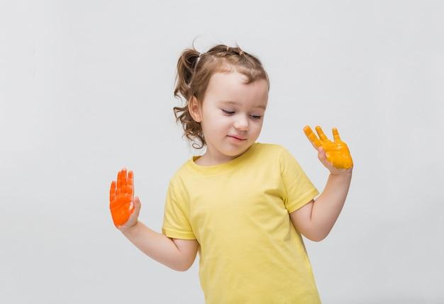 Fille douce avec des queues de cheval dans un t-shirt jaune avec ses mains en peinture. apprendre à dessiner