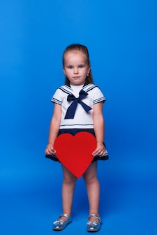 Fille douce et réfléchie enfant de 3 ans vêtue d'une robe bleue tenir dans la main coeur rouge isolé sur l'espace de mur bleu.