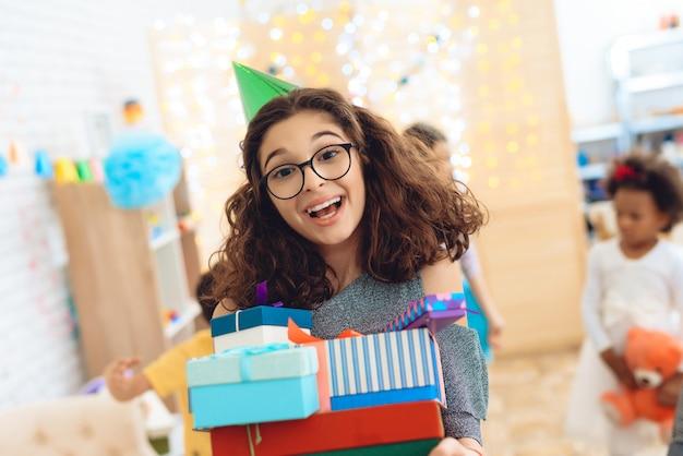Une fille douce se réjouit du grand nombre de cadeaux à son anniversaire.