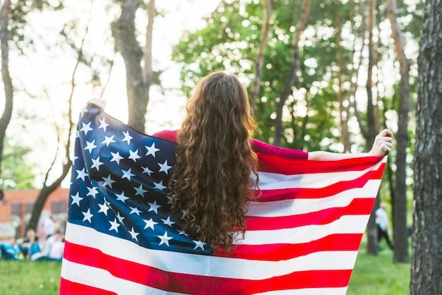 Fille avec un drapeau américain dans la nature