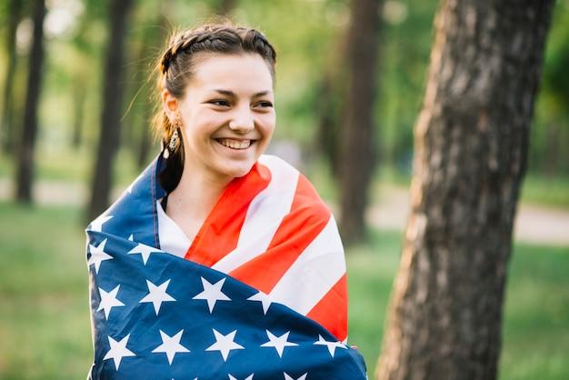Fille avec un drapeau américain en face de l'arbre