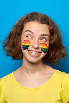 Fille avec drapeau fierté peint sur ses joues souriant