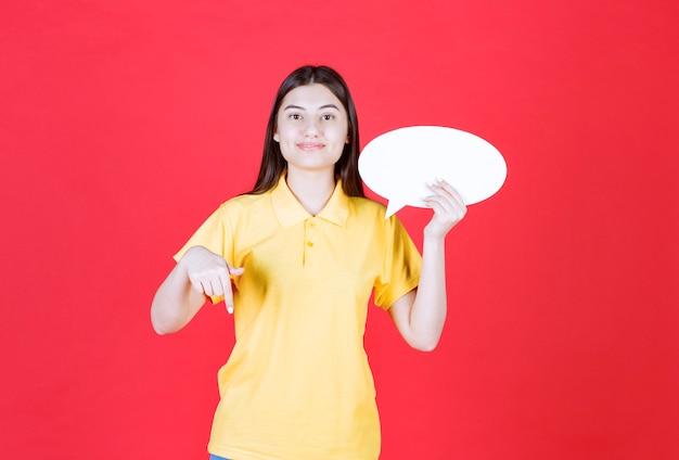 Fille en dresscode jaune tenant un panneau d'information ovale et appelant quelqu'un à côté d'elle