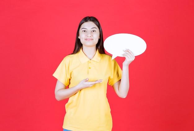 Fille en dresscode jaune tenant un panneau d'information ovale.
