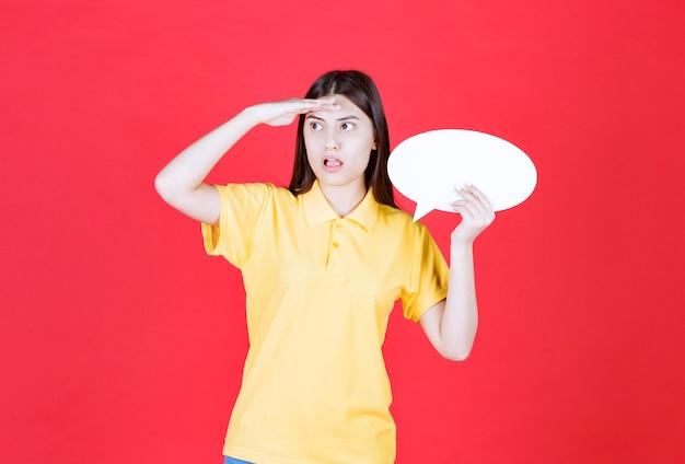 Fille en dresscode jaune tenant un tableau d'information ovale et a l'air réfléchie et hésitante.
