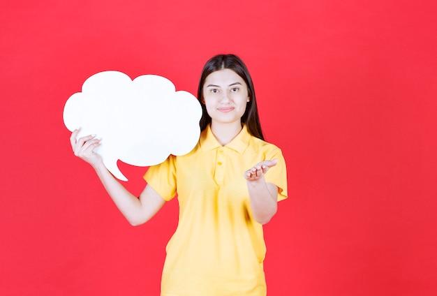 Fille en dresscode jaune tenant un tableau d'informations en forme de nuage et invitant quelqu'un à côté d'elle