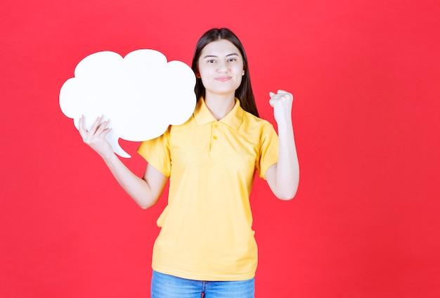 Fille en dresscode jaune tenant un tableau d'informations en forme de nuage et montrant son poing.