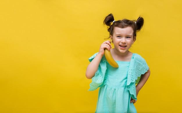 La fille drôle dans une robe bleue tient une banane sur un fond jaune avec une copie de l'espace