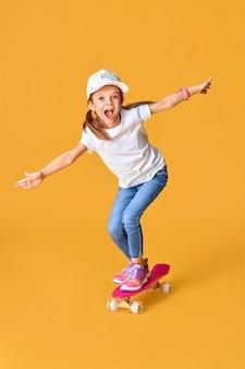 Fille drôle élégante portant un t-shirt blanc, un jean bleu et des baskets, debout sur une planche à roulettes sur un espace jaune