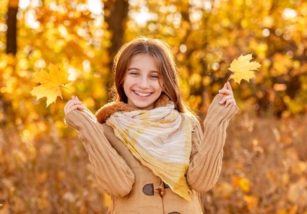 Fille drôle avec des feuilles d'automne couvrant son visage et sa langue