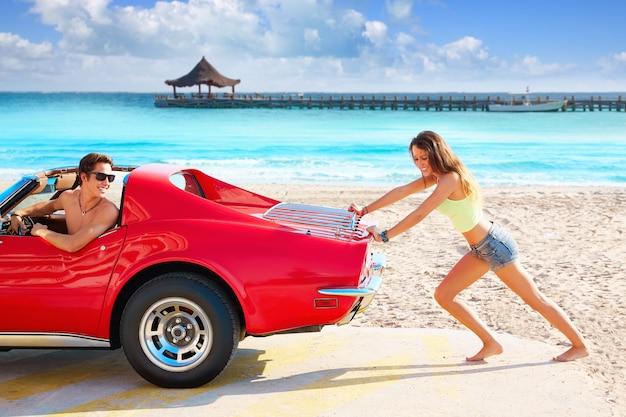 Fille drôle poussant une voiture cassée sur la plage