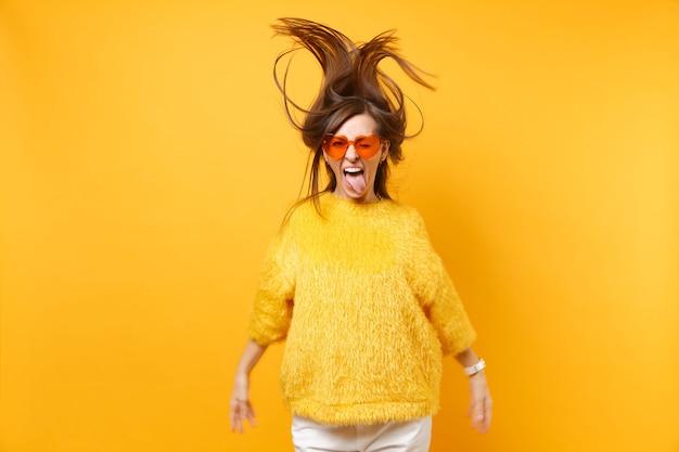 Fille drôle en pull de fourrure, lunettes orange coeur montrant la langue, s'amuser en saut de studio avec des cheveux flottants isolés sur fond jaune. les gens émotions sincères, mode de vie. espace publicitaire.