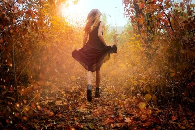 Fille drôle en robe noire en cours d'exécution dans la forêt d'automne d'or à l'extérieur