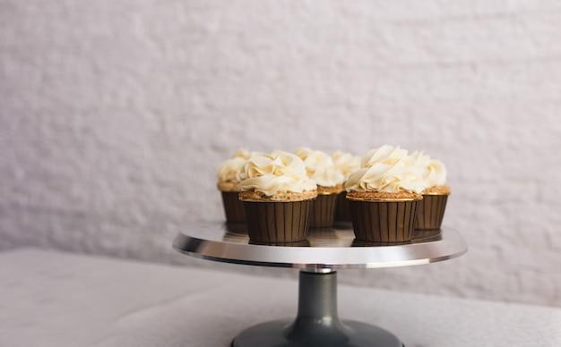La fille du chef saupoudre le glaçage sur des petits gâteaux frais recouverts de crème à la vanille.