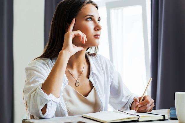 Une fille du millénaire est assise devant un ordinateur portable et étudie à distance. l'élève utilise des opportunités d'apprentissage à distance en ligne. les femmes améliorent leurs compétences et leurs connaissances grâce à la formation. pensive jeune femme regardant le webinaire.