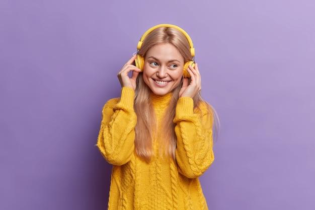 Fille du millénaire positive bénéficie d'une musique agréable via des écouteurs étant de bonne humeur sourit joyeusement vêtu d'un pull jaune équipé