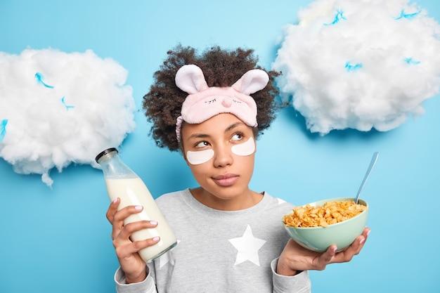 Une fille du millénaire réfléchie a un petit-déjeuner sain détient un bol de flocons de maïs et une bouteille de lait vêtue de vêtements de nuit applique des correctifs pour réduire les poches isolées sur le mur bleu