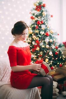 Fille du nouvel an avec un cadeau dans ses mains près de l'arbre de noël