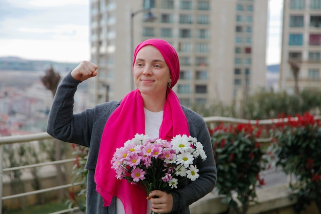 Fille en écharpe rose et masque blanc avec des marguerites à l'extérieur. concept de sensibilisation au cancer.