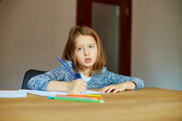 Fille de l'école de dessin et d'écriture d'une image avec des crayons de couleur, à l'aide de crayons de couleur à la table à la maison