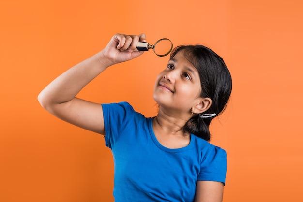 Fille de l'école indienne heureuse avec loupe, debout isolé sur fond orange