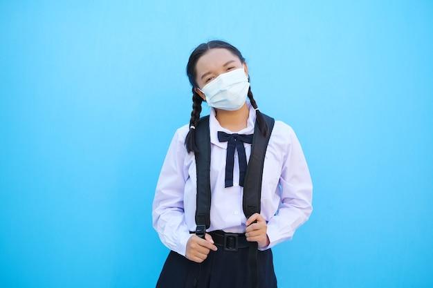 Fille de l'école porte un masque avec sac à dos sur fond bleu