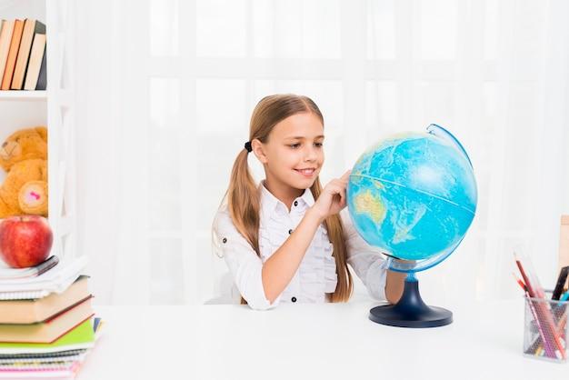Fille d'école primaire avec globe