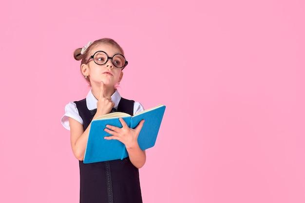 Fille de l'école primaire en uniforme, lunettes rondes sans lentilles tient un cahier dans ses mains avec une émotion réfléchie sur son visage, posant sur un espace rose dans le