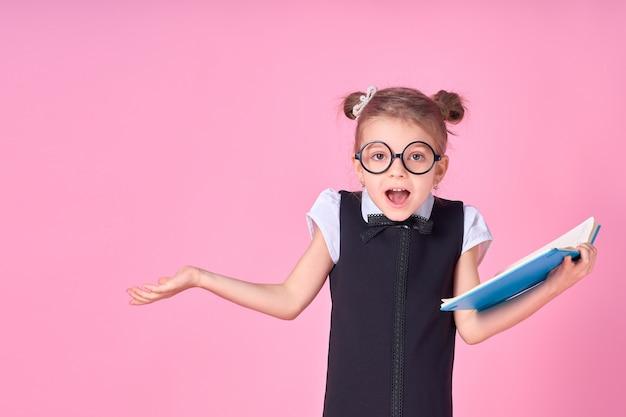 Fille de l'école primaire en uniforme, lunettes rondes sans lentilles tient un cahier dans ses mains et lève sa main sur le côté avec l'émotion d'une question sur son visage, posant sur un espace rose