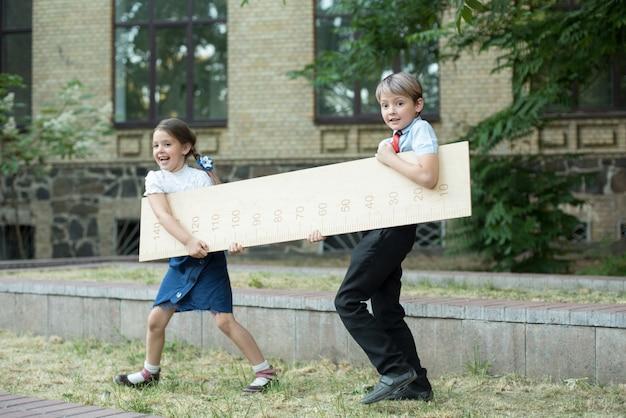 Fille et écolier avec une grande règle debout sur fond d'école