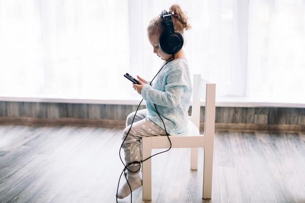 Fille écoutant de la musique sur la chaise