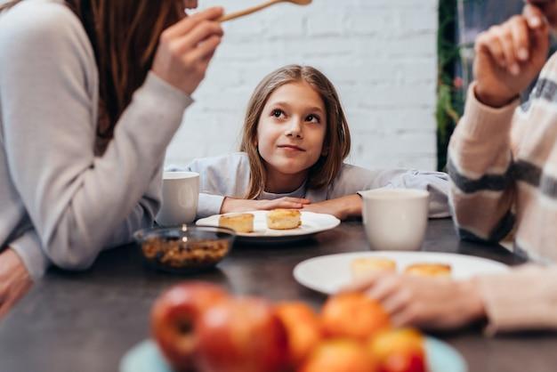Fille écoute des adultes parler ensemble à la table de la cuisine.