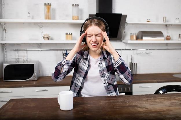 La fille écoute de la musique sur des écouteurs et boit du café. une femme a mal à la tête