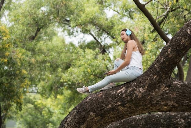 Fille écoute musique sur grand arbre de verdure