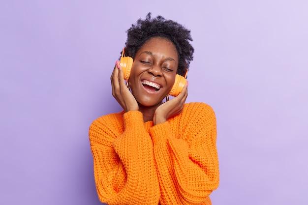 Une fille écoute de la musique via des écouteurs sans fil s'amuse vêtue d'un pull tricoté décontracté isolé sur violet