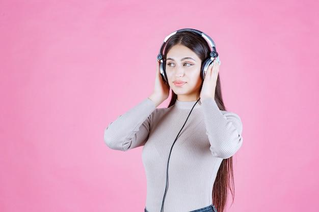 Fille avec des écouteurs, écouter de la musique et se sentir heureux