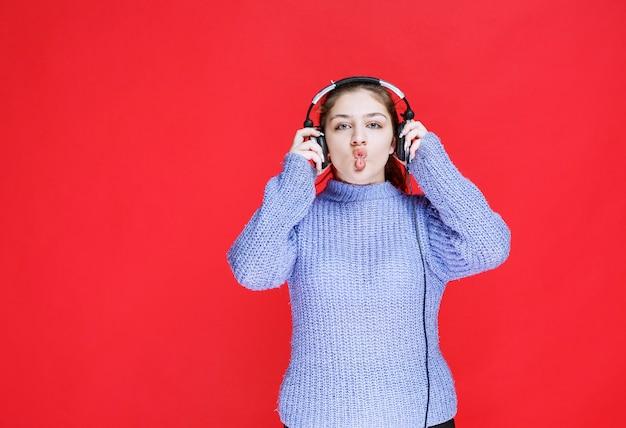 Fille avec des écouteurs mettant sa langue.