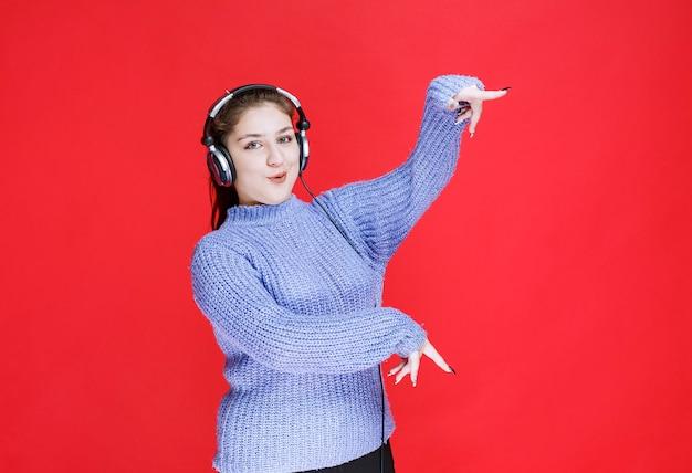 Fille avec des écouteurs pointant vers quelque chose sur la droite.