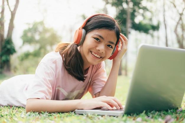 Fille avec des écouteurs sans fil écoute la musique dans le parc.