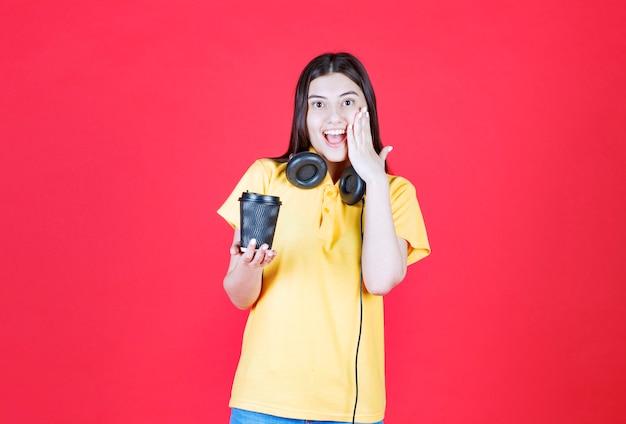 Fille avec des écouteurs tenant une tasse de boisson jetable noire, couvrant la bouche et a l'air surprise.