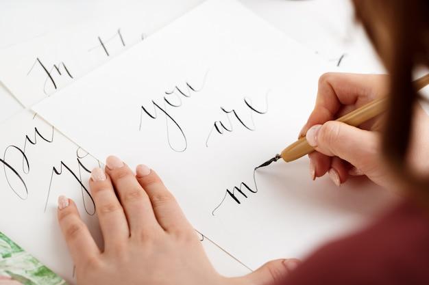 Fille écrit la calligraphie sur les cartes postales. conception d'art.