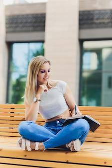 Fille écrit dans un cahier, assise sur un banc dans le parc.