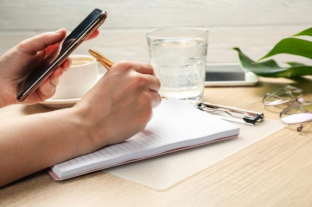 Fille écrit dans un cahier. concept d'entreprise ou de blogueur