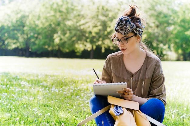 Fille écrit dans un cahier dans un champ.