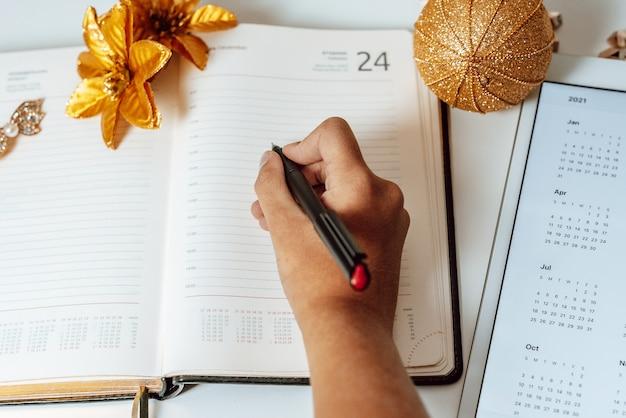 La fille écrit dans le journal à côté du calendrier pour 2021 sur tablette pc et casque sans fil, le concept de plans, la liste de souhaits et la liste des choses à faire avant noël