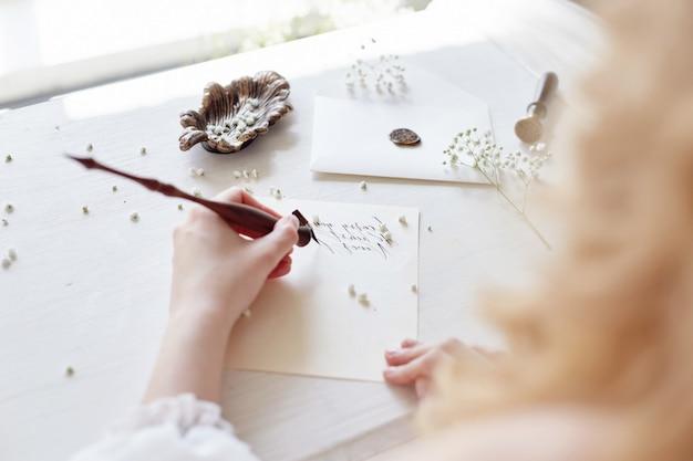 Fille écrit une lettre à son homme bien-aimé assis à la maison à la table dans une robe blanche, la pureté et l'innocence. look romantique blonde bouclée, beaux yeux