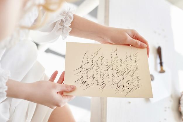 Une fille écrit une lettre à son homme bien-aimé, assise à la maison à table dans une robe blanche claire, pure et innocente. look romantique blonde bouclée, beaux yeux. fleurs sauvages blanches sur la table. corps parfait