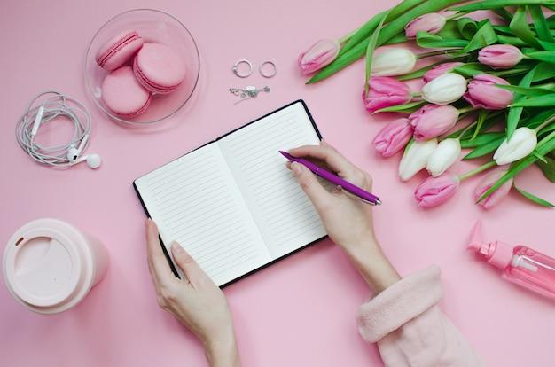 Fille écrit la liste de souhaits pour les plans futurs. composition plate avec des fleurs, un bloc-notes, une tasse de café et des bonbons